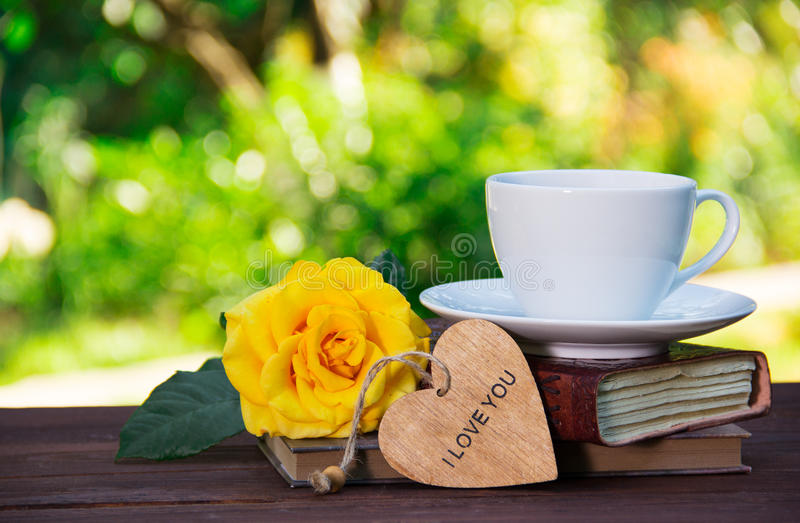 A cup of summer tea on a stack of books and a fragrant yellow rose. Romantic concept. Copy space stock photos