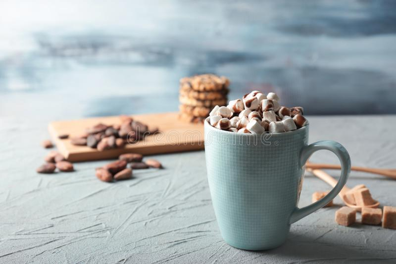Cup of tasty cocoa drink with marshmallow on textured table stock photography
