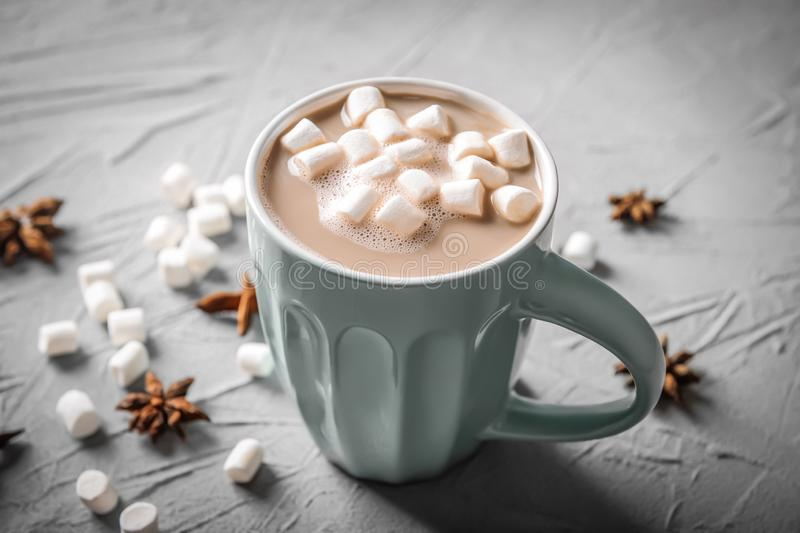 Cup of tasty cocoa drink with marshmallow on textured table royalty free stock images