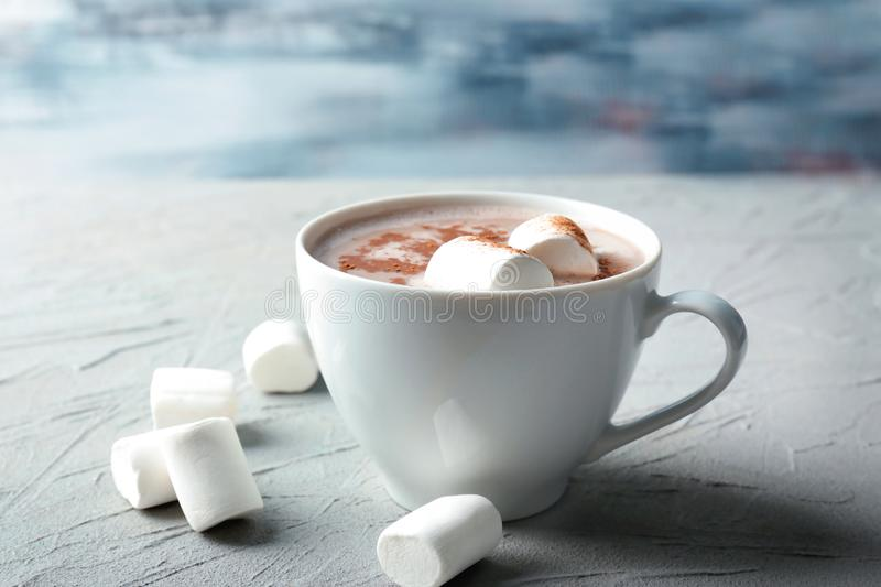 Cup of tasty cocoa drink with marshmallow on textured table royalty free stock photography