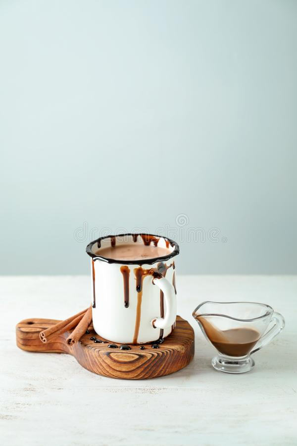 Cup of tasty cocoa and sauce boat on white table stock photography