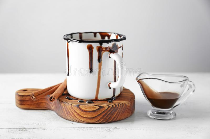 Cup of tasty cocoa and sauce boat on white table royalty free stock photo
