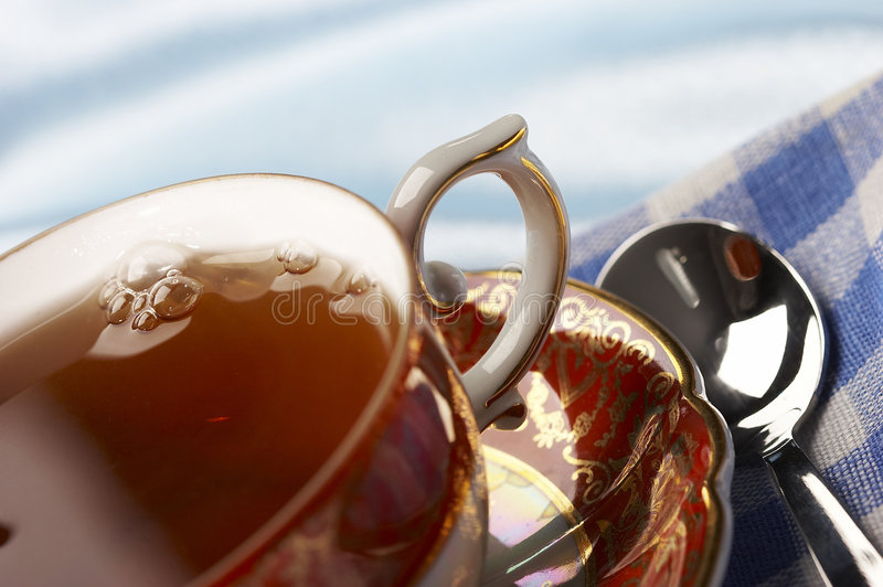 Cup of tea. Macro pic of cup of tea with spoon over blue background royalty free stock image