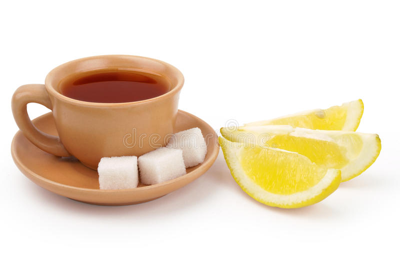 Cup of tea. A cup of black tea with shigar pieces and lemon slices isolated on white background royalty free stock photography