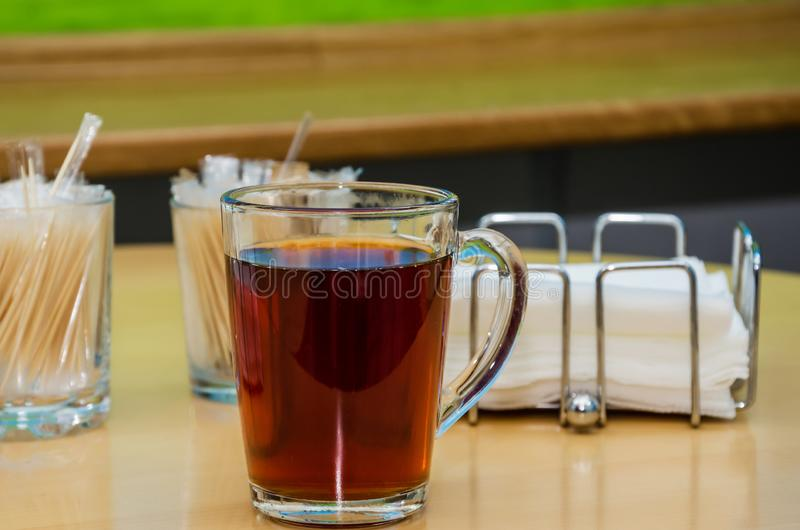 Cup of tea on a background of a wooden table, wooden sticks and napkins. Close-up. Cup of tea on a background of a wooden table, wooden sticks and napkins royalty free stock photo