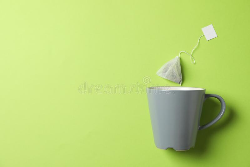 Cup and tea bag on green background stock photography