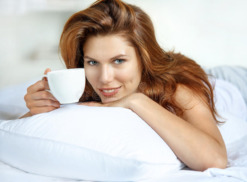 Cup of tea in bed. Beautiful brunette woman have a cup of tea lying in bed stock photography