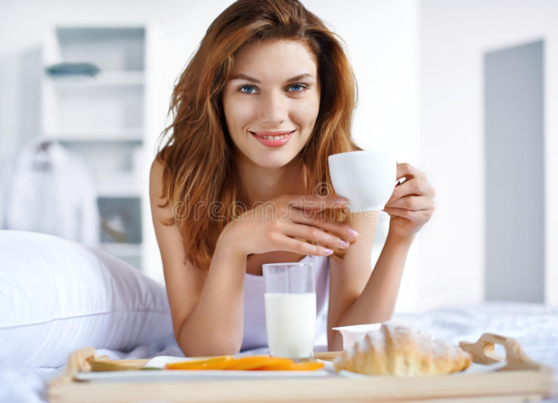Cup of tea in bed. Beautiful brunette woman holding white porcelain cup in hand and smiling lying in bed stock images
