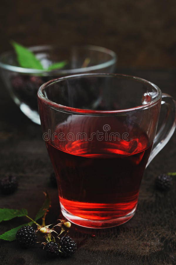 Cup of tea and black raspberries royalty free stock image