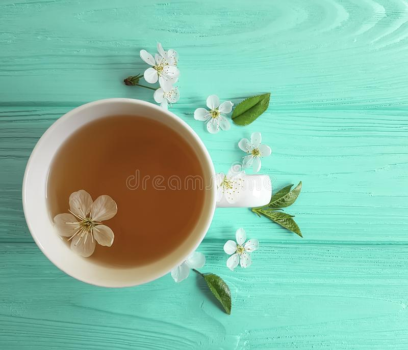 Cup of tea blossoming cherry, aroma vintage composition apricot on blue wooden background royalty free stock photography