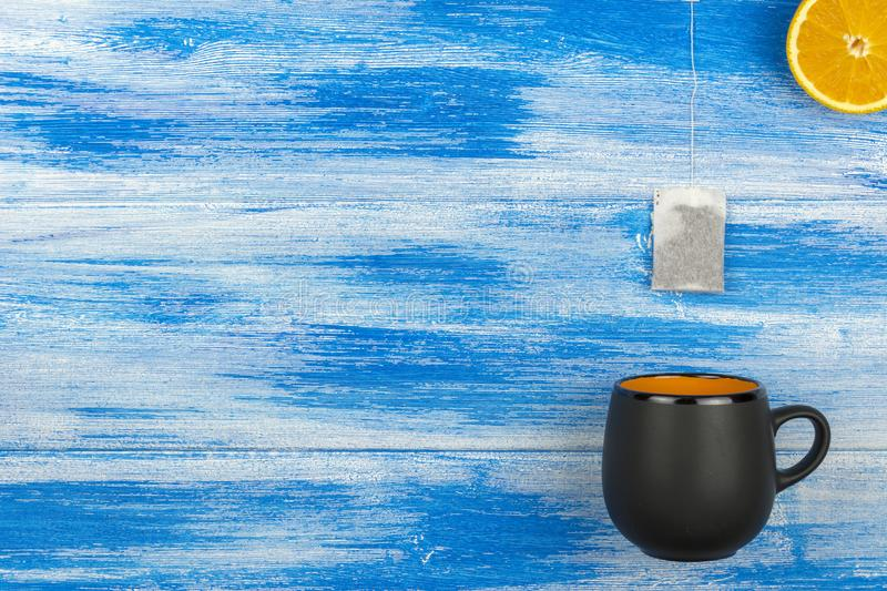 The Cup of tea on a blue background. Tea bag and orange slices. Summer royalty free stock photography
