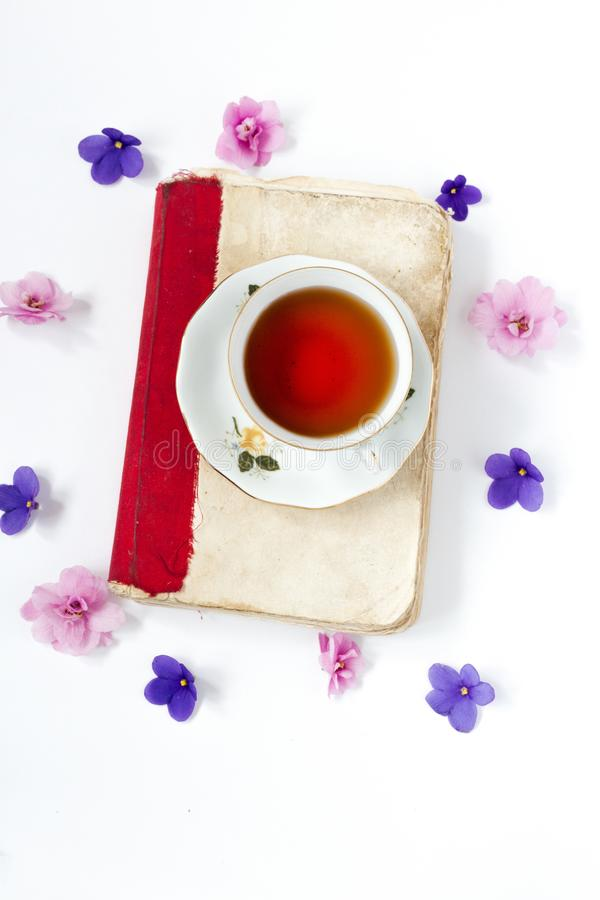 Cup of tea on book with flower over wite background . Cup of tea on book with flower over wite background royalty free stock photography