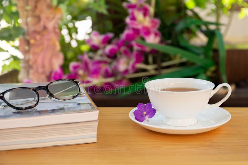 Cup of tea with books and eyes glasses on wooden table in garden. royalty free stock photography