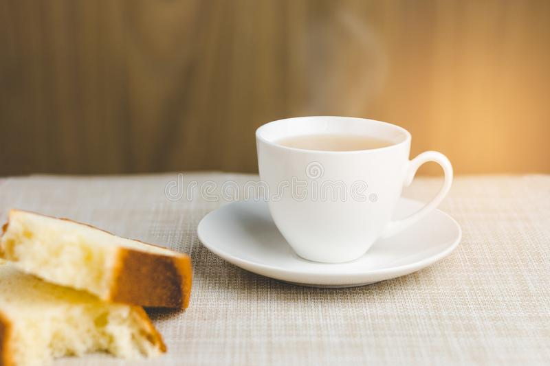 Cup of tea with bread for breakfast on wooden background stock images