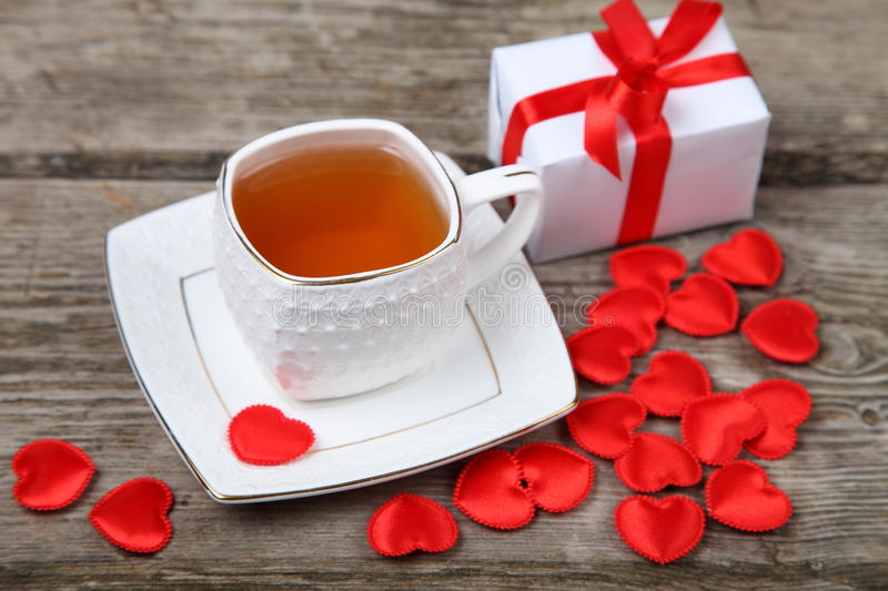 Cup of tea, cake and red hearts stock photos
