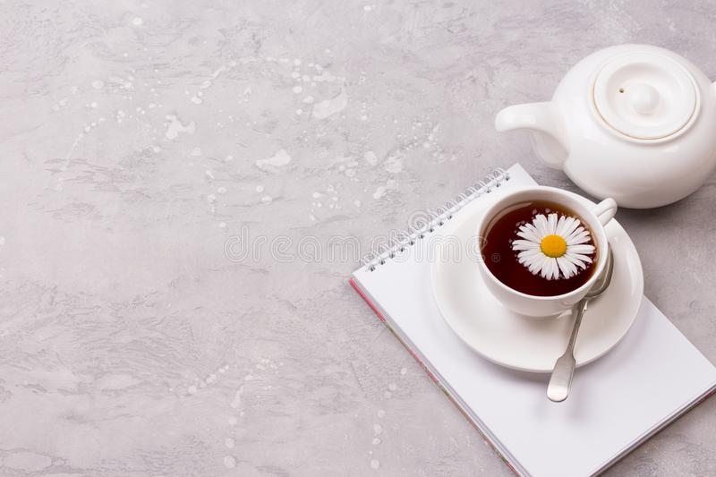 Cup of tea with chamomile flowers on grey stone background royalty free stock photos