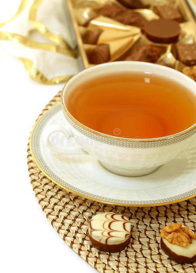 Cup of tea and chocolate pralines. On white royalty free stock photo