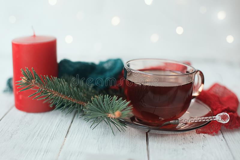 Cup of tea with Christmas decoration with pine candle lights and napkins on a white background. A cup of tea on a saucer with a spoon with a Christmas winter royalty free stock photos