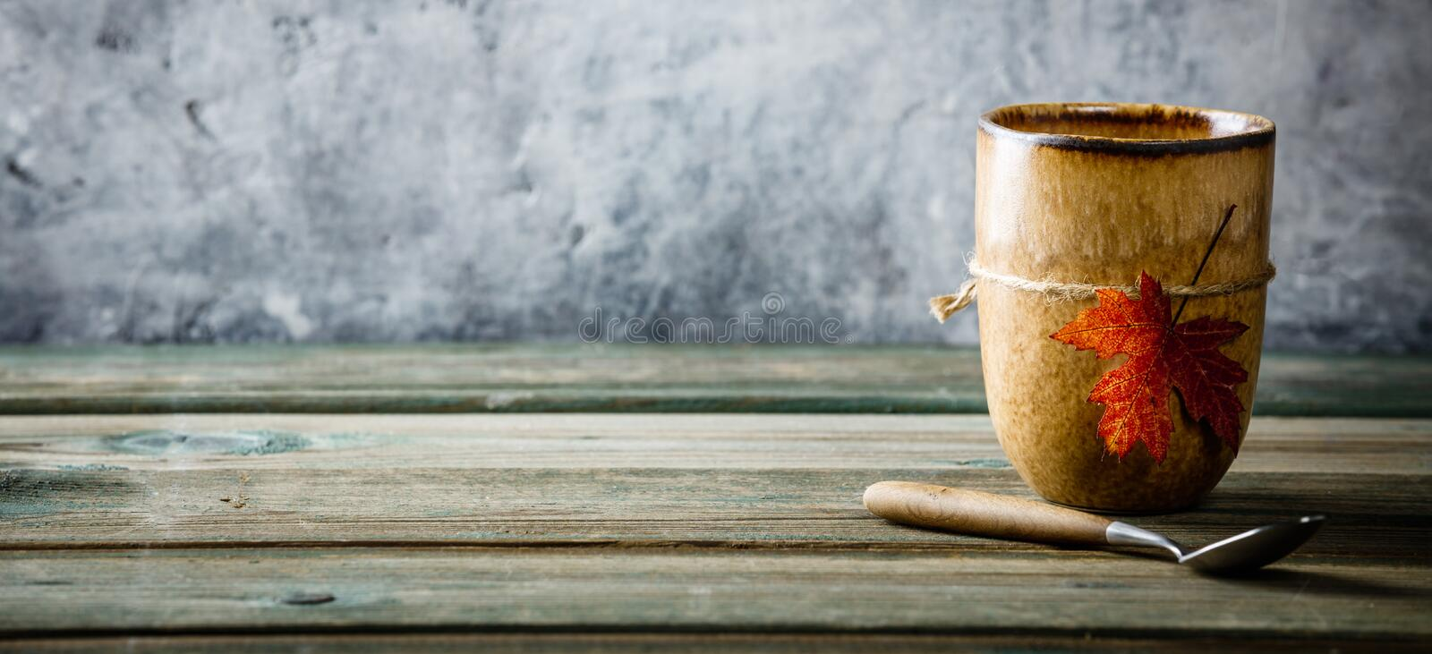 Cup of tea or coffee with autumn leaf royalty free stock image
