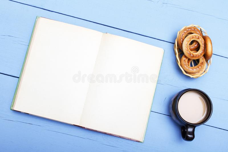 Cup tea, coffee and cookies, book with clean sheet on wooden table. Template copy space royalty free stock images