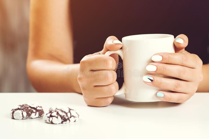 Cup of tea or coffee in female hands close up. Perfect woman manicure. Woman drinks tea, cookies on table. White cup in women`s stock images
