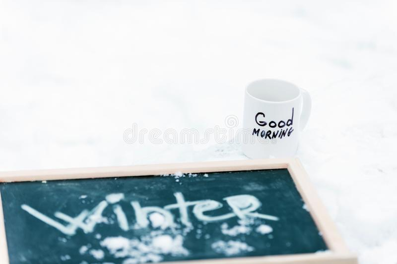 Cup of tea or coffee with Good Morning inscription. Blackboard with word Winter on it covered with snow. Chalkboard lying on snow near mug of beverage on white stock photos