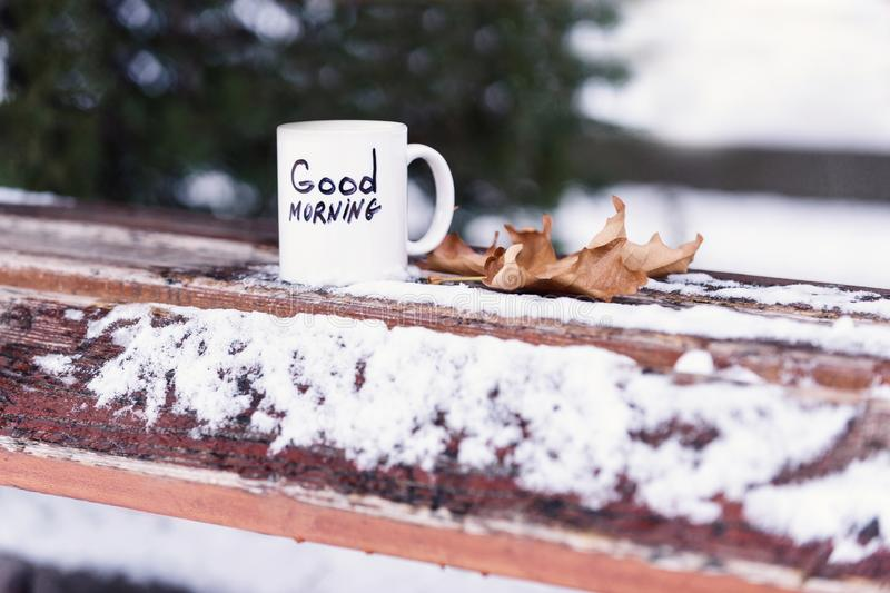 Cup of tea or coffee with Good Morning inscription. Drink on wooden board near autumn leaf. Winter morning drink concept. Mug of beverage on snow on natural royalty free stock photography