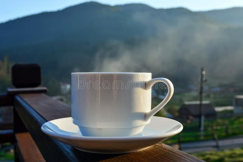 A cup of tea, coffee, standing on the porch of the hotel balcony, overlooking the mountains, in the early morning in the sunlight.  stock photo