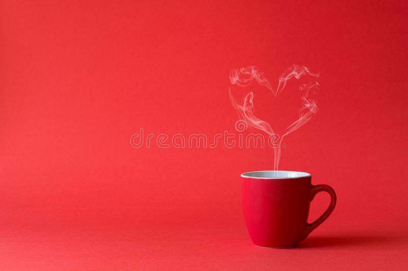 Cup of tea or coffee with steam in one heart shape on red background. Valentine`s day celebration or love concept. Copy space.  stock photography