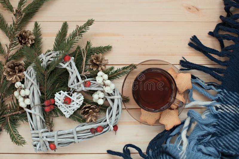 Cup of tea with cookies asterisks with a Christmas wreath heart of winter berries and blue with a white blanket royalty free stock photos