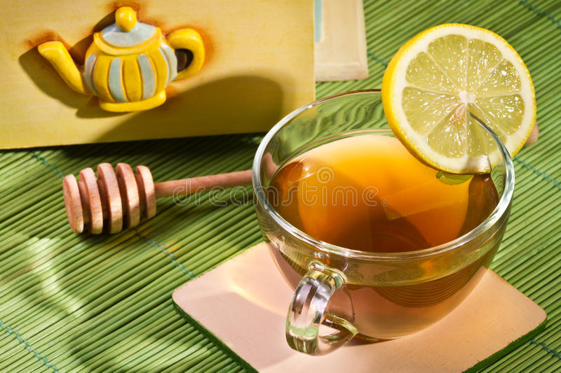 Cup of tea and Cupboard with honey dipper stock photography