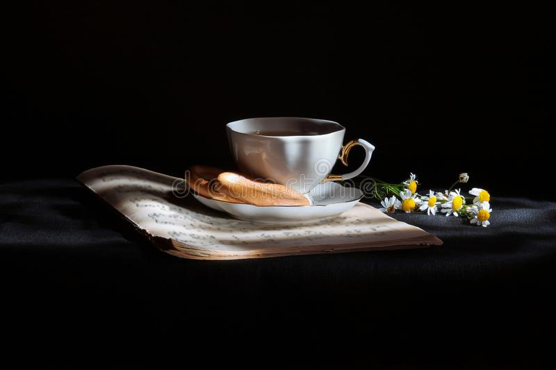 Cup of tea with daisies. Cup of tea, with pastry on the plate and with daisies, on a background of notes stock photos