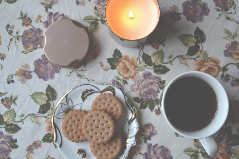 A cup of tea, dessert and lighted candle on the table. Morning breakfast. stock photo