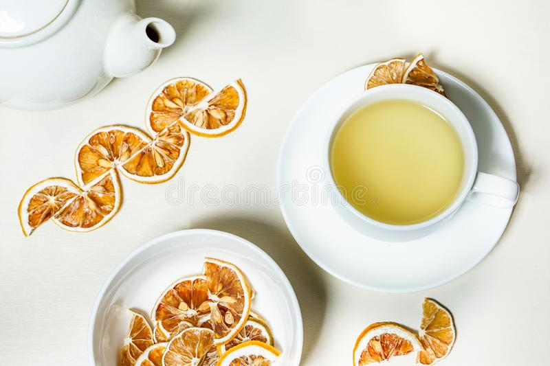 Cup of tea with dried lemon on the side and a bowl of dried lemon in the forcground and tea pot and the background. Isolated on white background. Close up stock photos