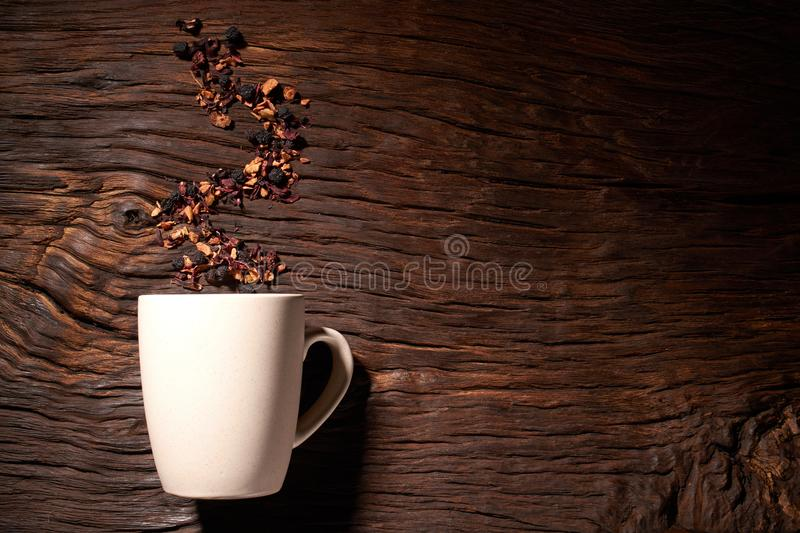 Cup of tea with dried tea leaf on the wooden background. A creative vapor of dry tea. Cup of tea with dried tea leaf on the wooden background stock photography