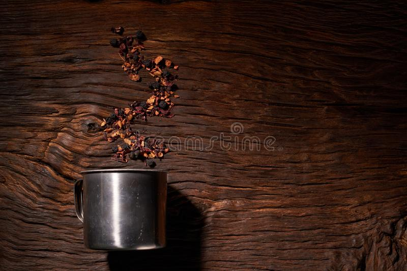 Cup of tea with dried tea leaf on the wooden background. A creative vapor of dry tea. Cup of tea with dried tea leaf on the wooden background stock image