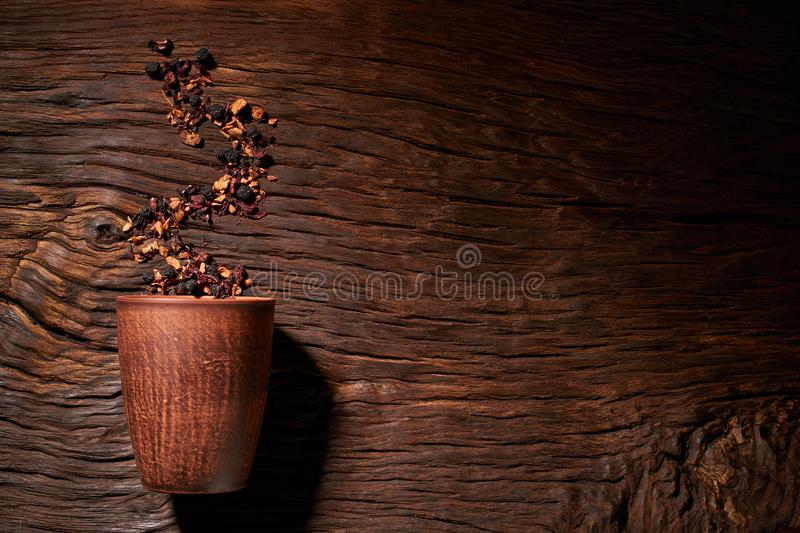 Cup of tea with dried tea leaf on the wooden background. A creative vapor of dry tea. Cup of tea with dried tea leaf on the wooden background royalty free stock images