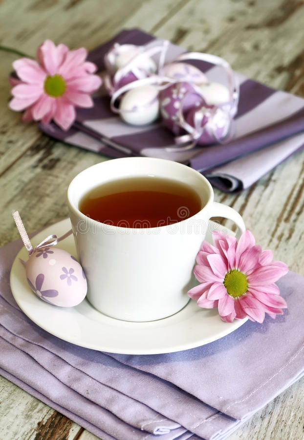 Cup of tea, easter eggs and chrysanthemums on old stock photography