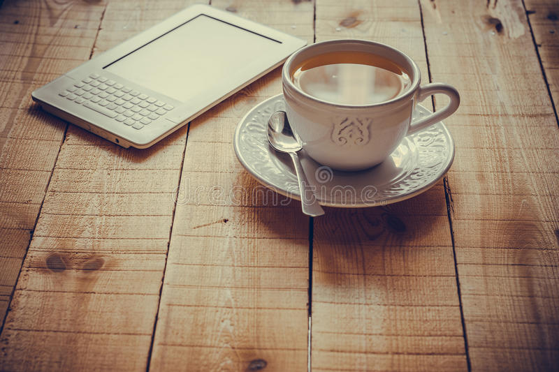 A cup of tea and an ebook reader on a wood table. In retro style, toned, postcard template or background for blog, magazine stock photography