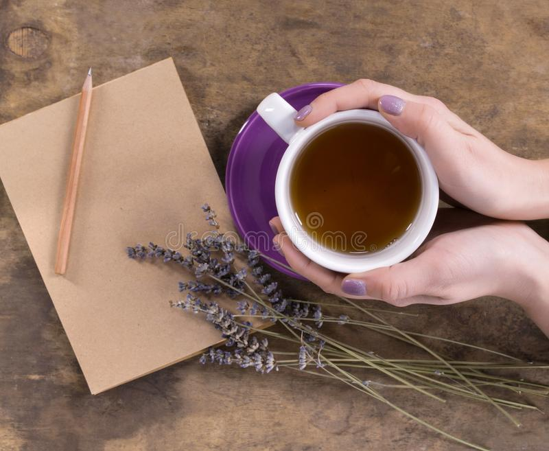 A cup of tea in female hands, lavender and notebook with pencil stock photos