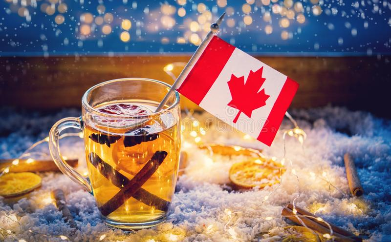 Cup of tea and flag of Canada on snow and fairy lights. Background. Christmas time decoration royalty free stock images