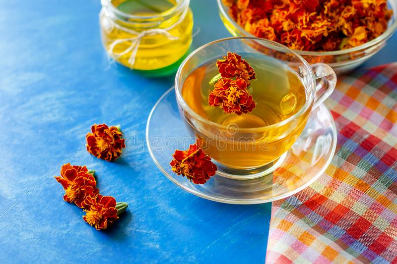 A cup of tea from the flowers of Chernobrivtsov. Processing of dried flowers marigolds. A cup of tea from the flowers of Calendula and Chernobrivtsov. Processing royalty free stock image