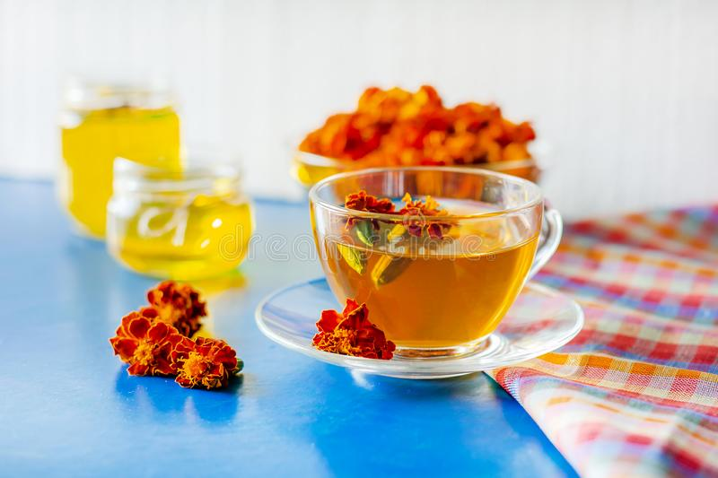 A cup of tea from the flowers of Chernobrivtsov. Processing of dried flowers marigolds. A cup of tea from the flowers of Calendula and Chernobrivtsov. Processing stock photography