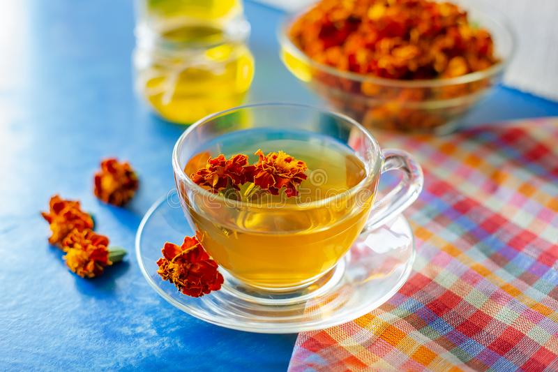 A cup of tea from the flowers of Chernobrivtsov. Processing of dried flowers marigolds. A cup of tea from the flowers of Calendula and Chernobrivtsov. Processing stock photos