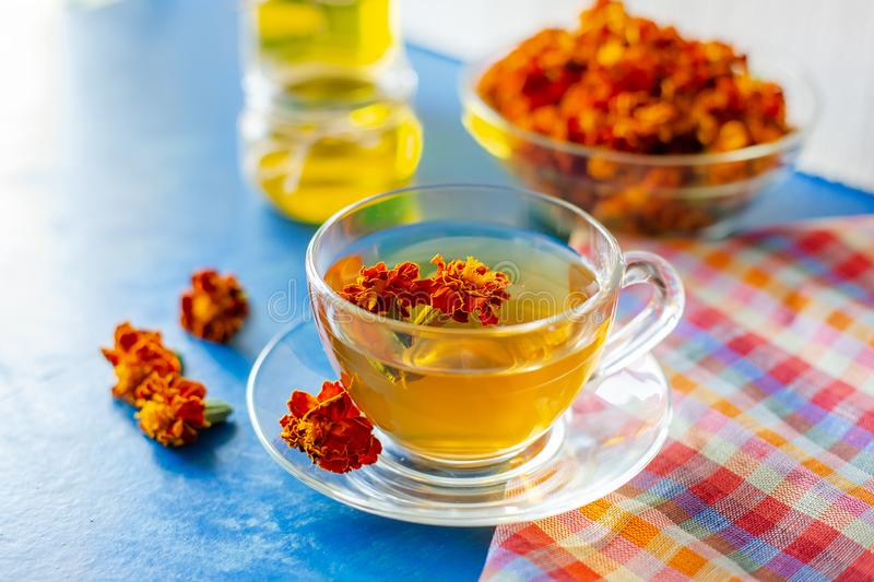 A cup of tea from the flowers of Chernobrivtsov. Processing of dried flowers marigolds. A cup of tea from the flowers of Calendula and Chernobrivtsov. Processing stock image