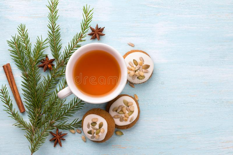 A cup of tea with fragrant honey Christmas gingerbreads with glaze and nuts, with Christmas tree branches and spices. On a light blue background, free space royalty free stock photography
