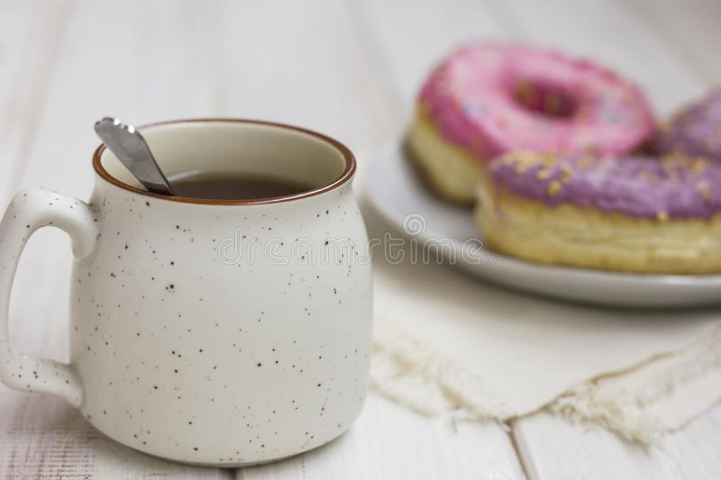 Cup of tea and fresh donuts in the white plate on wooden background. The cup of tea and fresh donuts in the white plate on wooden background stock images