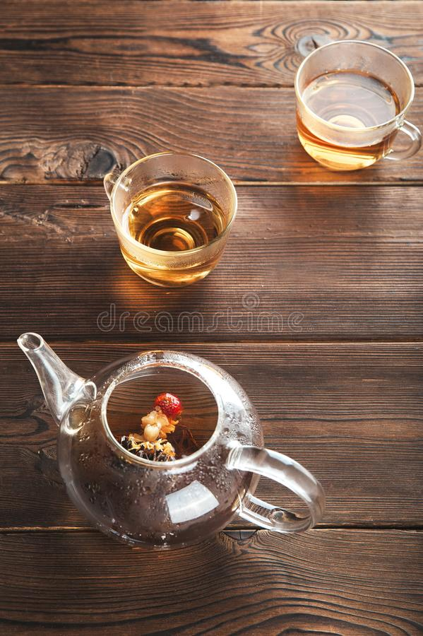A cup of tea with fresh leaves of green and black tea on a textural dark wooden background with copy space. Flower tea in a glass royalty free stock images