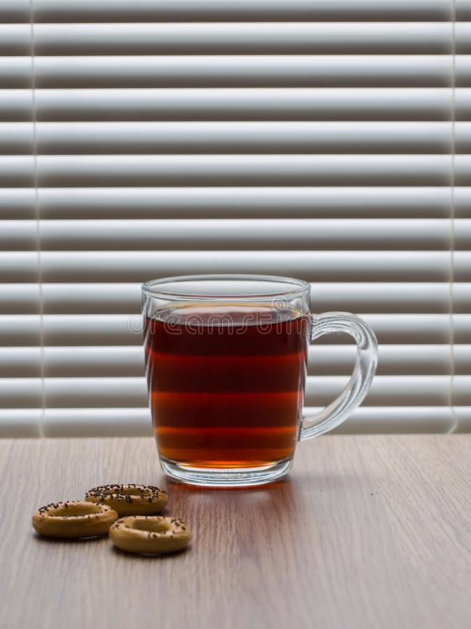 Cup of tea. Glass cup of black tea with bagels stock photos