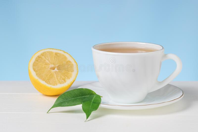 A Cup of tea with half a lemon on a white table on a blue background. royalty free stock image